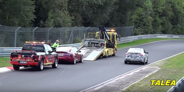 A Tesla Model S sat behind a tow truck on the Nürburgring as a Porsche Taycan drove past it
