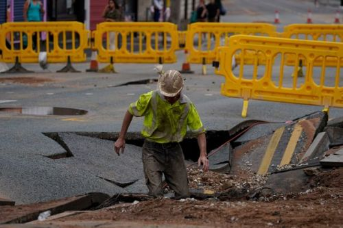 Dramatic photos show scale of damage as huge 15ft wide sinkhole opens in street
