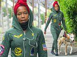 Regina King takes a walk with her dog Cornbread while wearing a red head wrap and green flight suit