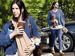 Scout Willis dons a monochromatic blue outfit as she carries multiple drinks and her dog