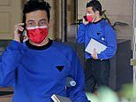 Rami Malek color blocks in blue sweatshirt and red face mask heading to his car inWest Hollywood
