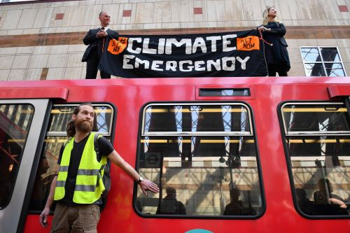 Three charged after climate change protesters glued themselves to trains