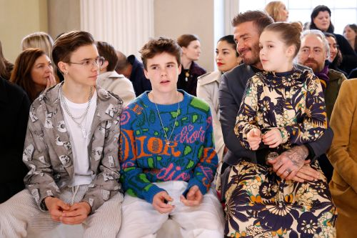 Proud David Beckham beams beside Harper, Romeo and Cruz as they support Victoria at London Fashion Week
