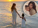 Kylie Jenner and Stormi walk in water in sunset photo