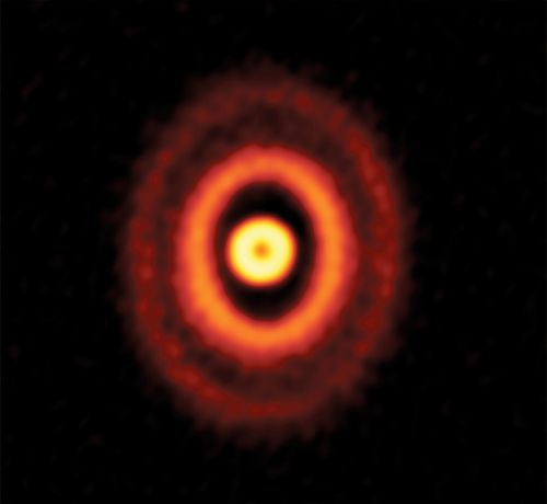 Triple star system features mis-aligned planet-forming dust rings