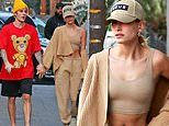 Hailey Bieber flaunts her taut midriff as she holds hands with husband Justin on a stroll in LA