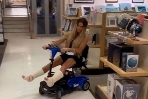Katie Price speeds around with her legs spread as she jokes over broken feet