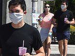Henry Golding has his hands full with two drinks as he joins his wife Liv Lo for errands