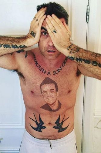 Robbie Williams reveals bizarre tattoo of his FACE on his own chest in shocking topless shot