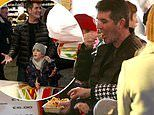 Simon Cowell breaks his vegan diet to tuck into some chips as he takes son Eric to Winter Wonderland