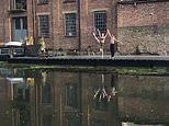 Ballet dancers perform a duet on London canalside to audience on the opposite bank
