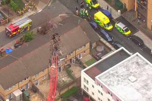 Victim of crane collapse named as woman, 85, as police try to recover body