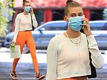 Hailey Bieber shows off her toned physique in orange leggings
