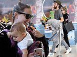 Kate Hudson is one happy mom as she carries baby Rani Rose through JFK airport with beau Danny