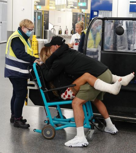 Katie Price's new man Carl Woods plays nurse as he gently lifts her from her wheelchair as they arrive home from Turkey