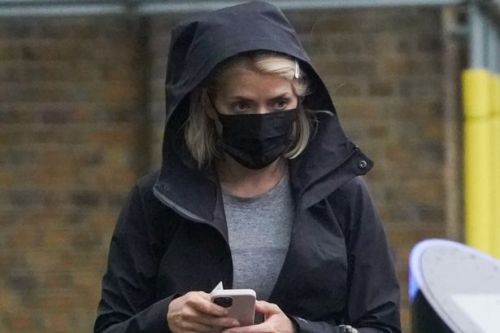 Holly Willoughby braves pouring rain in gym leggings and black hooded jacket