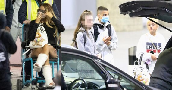 Katie Price wheeled out of airport as she arrives back in UK after breaking both feet