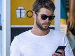 Liam Hemsworth looks unimpressed as he checks his phone in Byron Bay