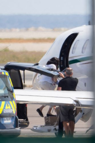 'Eco-warrior' Meghan Markle carries son Archie Harrison onto private jet after lavish break at Elton John's £15m palace in France with Prince Harry