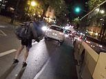 Man rollerblades while carrying a young child in his arms through the dark streets of Paris