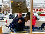 Man holds sign outside emergency room window thanking staff for 'saving my wife's life'