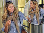 Elle Macpherson, 55, looks tense before she boards a yacht next to the iconic Sydney Opera House