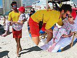 Lifeguards CARRY 95-year-old woman to beach chair when her wheelchair couldn't move through the sand