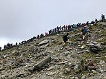 Hundreds of walkers cram onto Snowdon and queue without social distancing for a photo at the summit