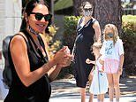 Gal Gadot covers her belly under a figure-hugging black dress while out to lunch with her daughters