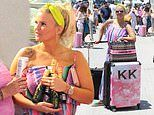 Kerry Katona cradles champagne bottles ahead of boarding a flight home from Mykonos