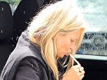 Kate Moss lights a cigarette in the rain ahead of flight to London at Mallorca airport