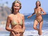 Lady Victoria Hervey looks sensational in a tiny gold bikini playing with a dog on the beach