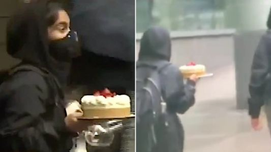 Moment masked looter strides out of ransacked restaurant with huge cheesecake