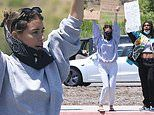 Madison Beer holds up two Black Lives Matter signs while protesting along a highway in Malibu
